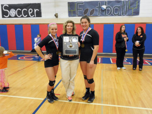 Seniors, Bekah and Kyla display trophy with Coach Campbell
