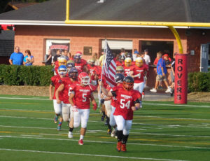 """(Photos submitted by Staub family) Will, bearing the """"Stars and Stripes,"""" leading the KSAC All-Stars onto the field"""